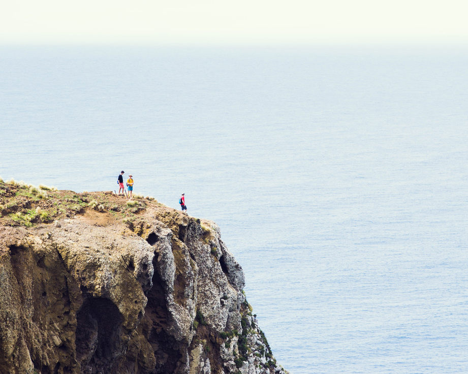 A few tiny figures exploring the end of a cliff over an endless sea.