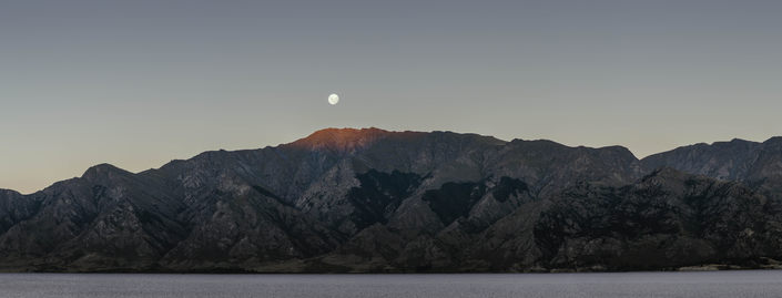 A wide panorama of the moon over a mountain ridge, and Lake Wanaka.