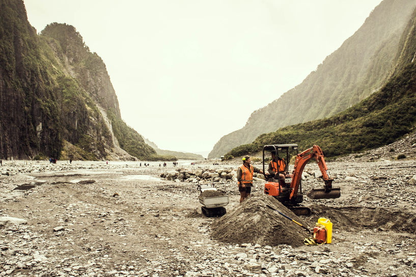 Workers in a mini-backhoe doing a tiny amount of earth moving in the middle of a vast glacial valley.