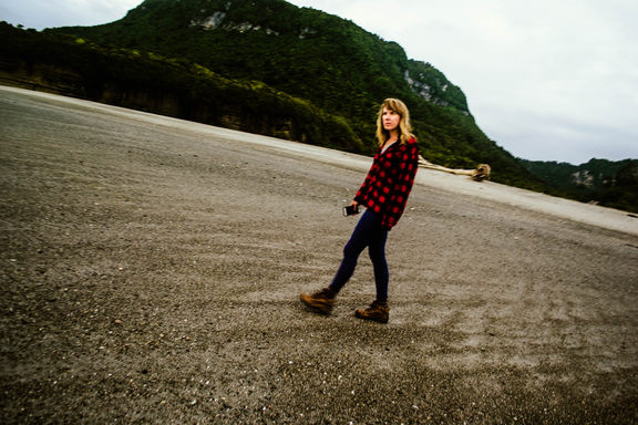 Tilted, motion-blurry photo of Britt walking on the beach in a flannel, hiking boots, and tights.