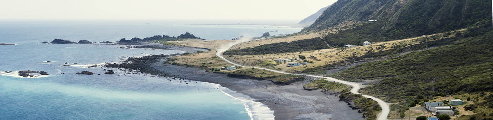 Panoramic image of a dusty road winding across a coastline.