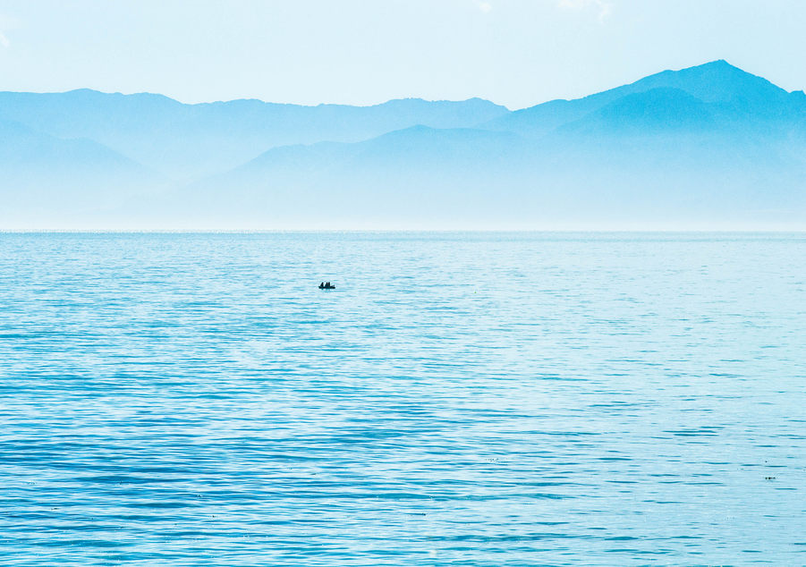 A tiny boat in a turquoise blue sea. Hazy blue mountains behind.