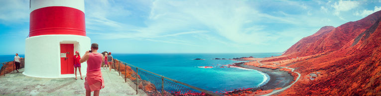 A wide panorama of the view from the top of the lighthouse; Sam is taking a photo of Britt infront of it.