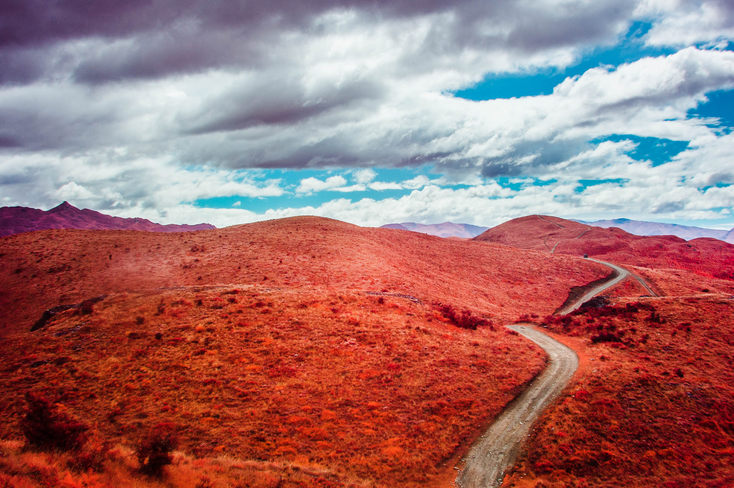 Rolling red hills, partly cloudy, a winding dirt road.