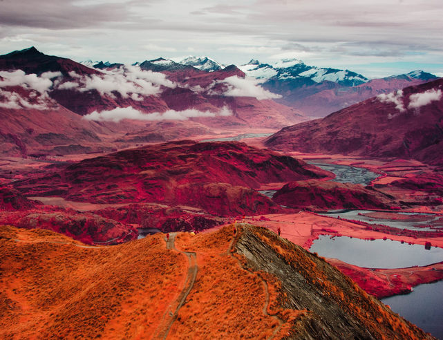 A huge red vista, mountains, lakes, clouds, a valley.
