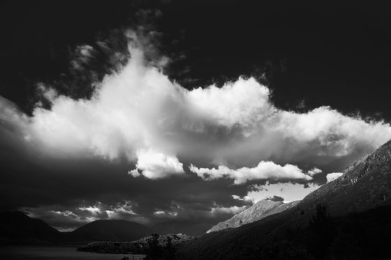 Towering bright white clouds on a black sky, lakes and a mountain.